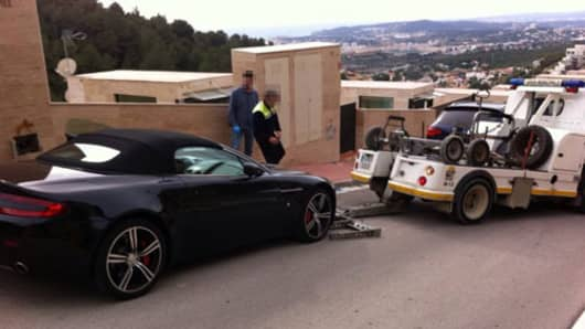 An Aston Martin is towed away from alleged fraudster's home in Barcelona